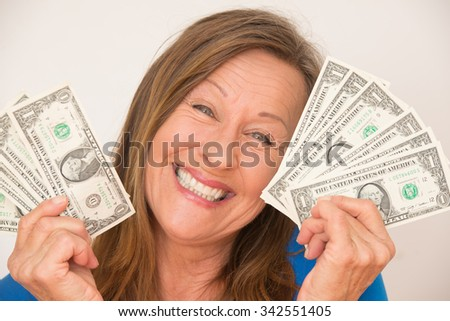 Portrait relaxed attractive mature woman holding happy smiling us dollar notes, isolated, bright background.
