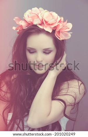 portrait romantic of beautiful woman with long curly brown hair wearing pink flower crown - stock photo