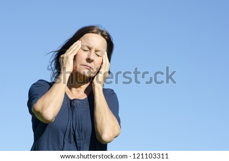 Portrait sad and stressed mature woman suffering migraine headache, isolated with blue sky as background.