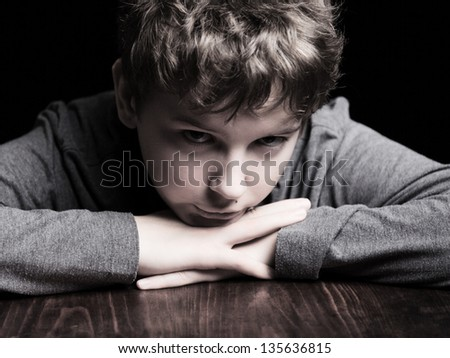Portrait sad teenage boy on a black background