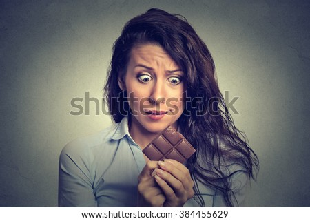 Portrait sad young woman tired of diet restrictions craving sweets chocolate isolated on gray wall background. Human face expression emotion. Nutrition concept. Feelings of guilt. Funny looking girl