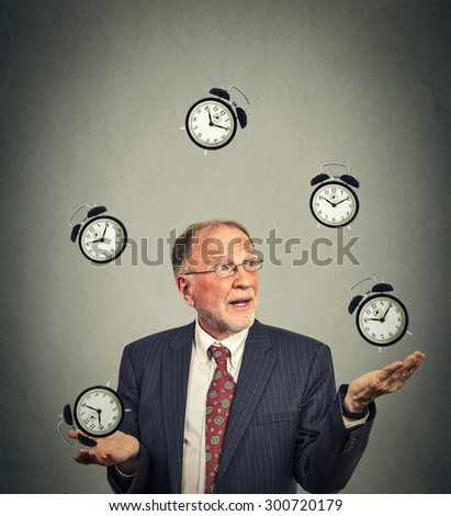 Portrait senior business man in suit juggling multiple alarm clocks isolated on gray office wall background. Timing concept  - stock photo