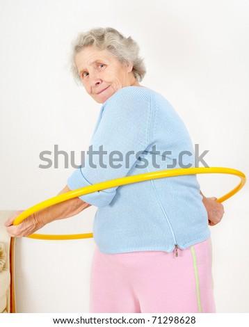 portrait senior lady doing gymnastic with hula-hoop - stock photo