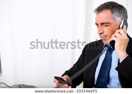 Portrait senior male waiting on telephone at the office - stock photo