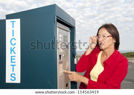 Portrait senior woman at ticket machine outdoor, isolated with blurred background of car park and cloudy sky - stock photo