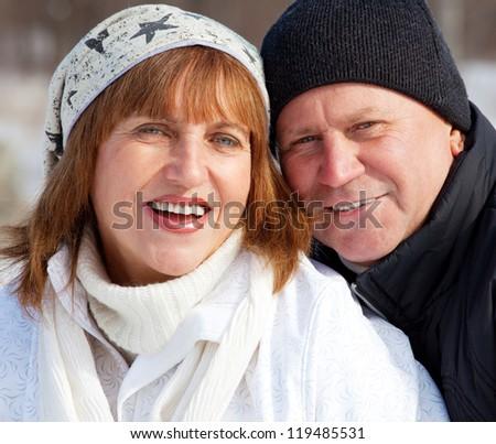 Portrait seniors couple in winter park. Elderly mature people - stock photo