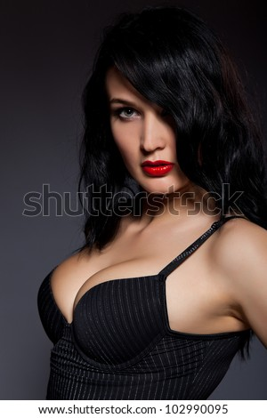 portrait sensual beautiful woman make up curly hair style, wear sexy corset, big breast, over dark black background