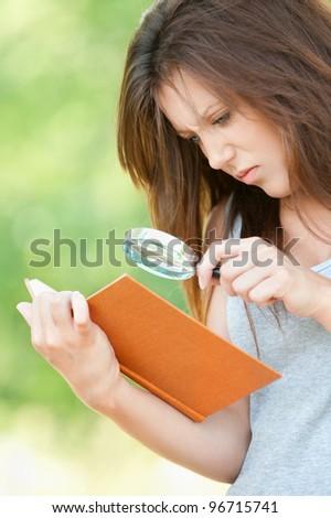 Portrait serious beautiful young woman magnifier regards book at summer green park - stock photo