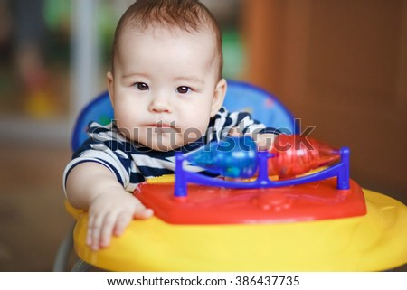 Portrait serious stern baby behind the wheel of a toy car. - stock photo