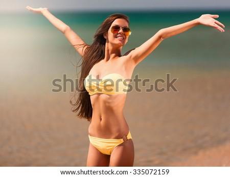 Portrait sexy beautiful brunette hair woman, has yellow bikini,  sunglasses, slim tan body, fun happy face. Posing in tropical hot sea. Luxury resort. Travel lifestyle. Nature sunny day. - stock photo
