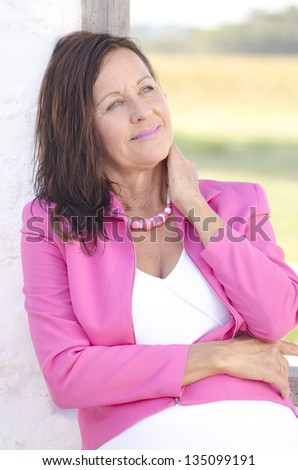 Portrait sexy confident and happy relaxed mature woman posing outdoor in pink jacket, smiling and joyful, with blurred background.