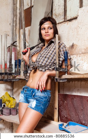 Portrait sexy girl in the carpentry shop carpenters - stock photo