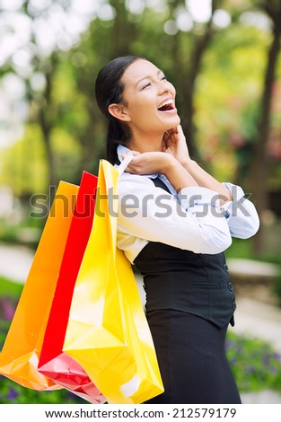 Portrait Shopping woman in Washington DC City. Beautiful model happy, smiling summer shopper holding shopping bags walking outside background outdoor park. Positive emotions, facial expressions. - stock photo