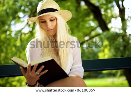 Portrait shot of a beautiful young woman in the 20s reading a book. She's sitting on a park bench. - stock photo