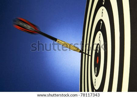 Portrait shot of a dart on bullseye of a dart board - stock photo