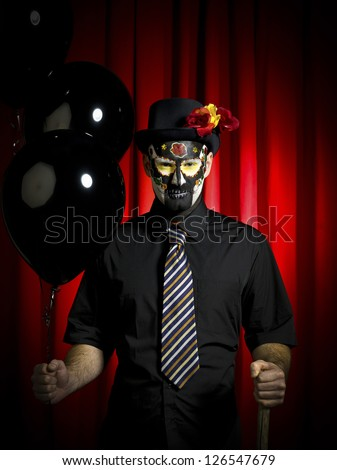 Portrait shot of a man wearing sugar skull and holding black balloons. - stock photo