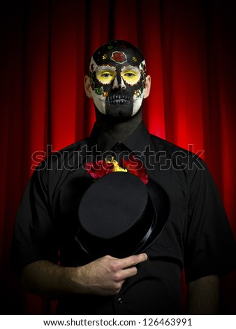 Portrait shot of a ugly man wearing sugar skull paint posing with hat in hand. - stock photo