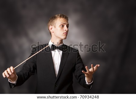 Portrait shot of a young orchestra conductor directing with his baton in a classical concert.