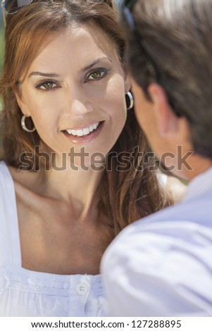 Portrait shot of an attractive, successful and happy middle aged man and woman couple in their thirties, sitting together outside in sunshine and smiling. - stock photo