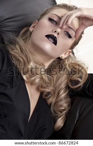 portrait shot of an elegant blonde curled girl wearing black lipstick and black eyeliner - stock photo