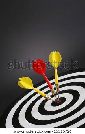 Portrait shot of three darts on bull's eye of a dart board - stock photo