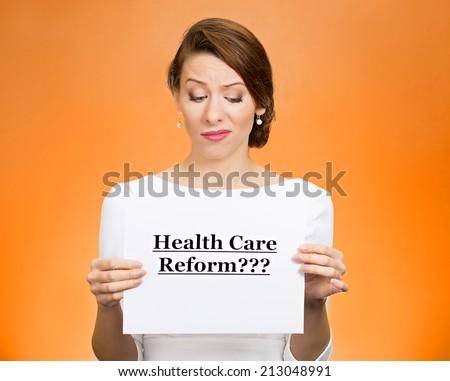 Portrait skeptical female, citizen, professional, doctor, holding sign health care reform? isolated orange background. Obamacare, medicaid, legislation debate insurance plan coverage concept.  - stock photo