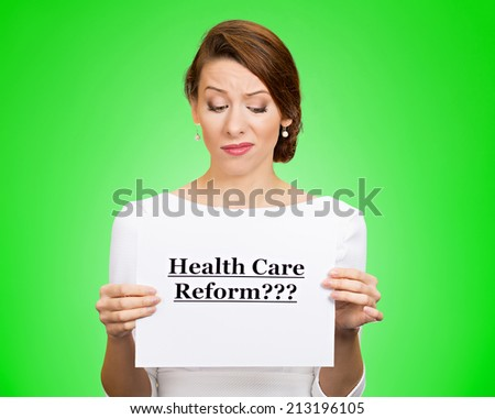 Portrait skeptical female, citizen, professional doctor holding sign health care reform with question isolated green background. Obamacare, medicaid, legislation debate insurance plan coverage concept - stock photo