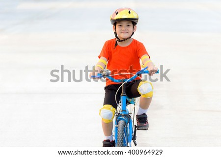 Portrait smart Asian kid to enjoy and happy  ridding bicycle at public garden