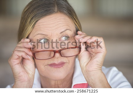 Portrait smart attractive mature business woman with glasses and curious observing expression, blurred background. - stock photo