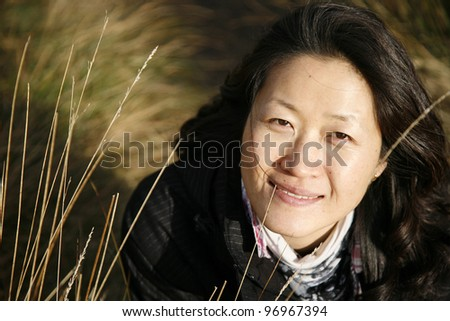 Portrait smiling asian woman looking up camera in the field