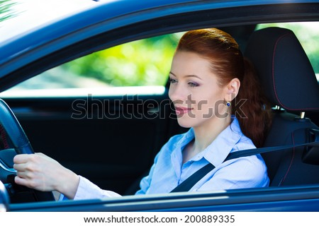Portrait smiling, attractive brunette woman, buckled up, driving, testing her new black car, automobile, purchased at dealership, isolated street, city traffic background. Safe driving habits concept - stock photo