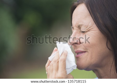 attractive mature woman suffering from cold or flu infection, sneezing ...