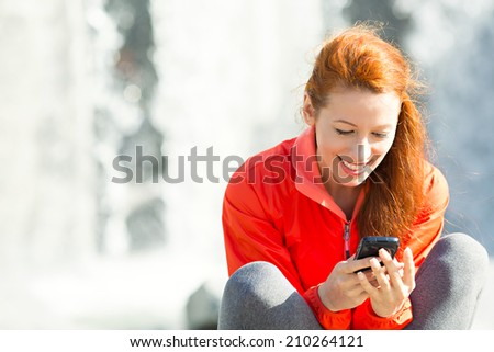 Portrait smiling beautiful city lifestyle woman on phone, pretty young girl texting on smartphone, isolated waterfall  background. Positive facial expression, emotions, communication concept. - stock photo