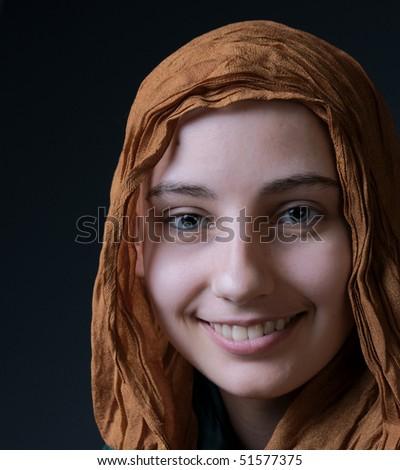 portrait smiling cancer survivor girl in silk scarf on grey background - stock photo
