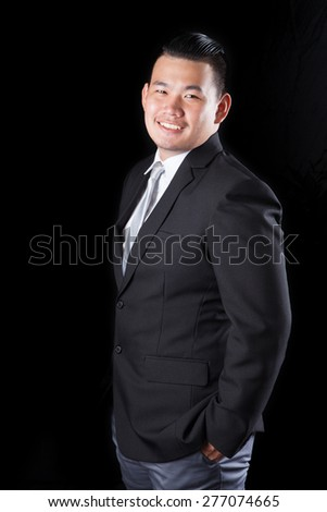 portrait smiling face with successful happiness emotion young asian man wearing western suit against black background with studio lighting