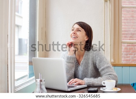 Portrait smiling middle aged woman sitting at cafe with laptop