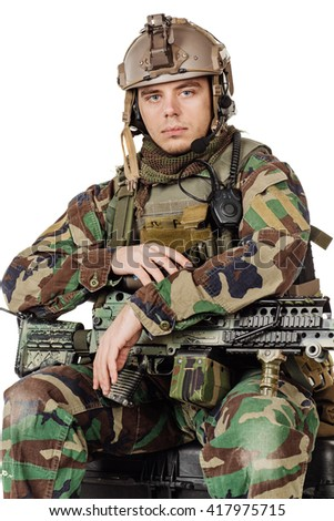 Portrait soldier or private military contractor holding with a machine gun and sitting on plastic black case. war, army, weapon, technology and people concept. Image on a white background.