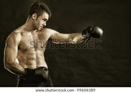 Portrait sportsman boxer in studio against dark background