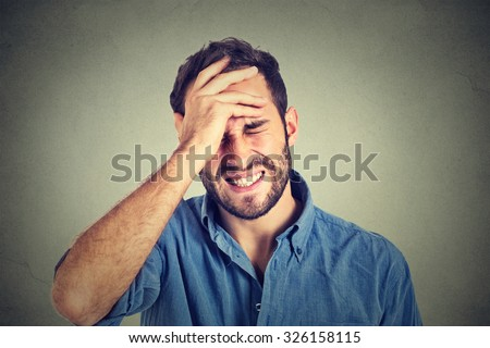 Portrait stressed man suffering from headache isolated on gray wall background - stock photo