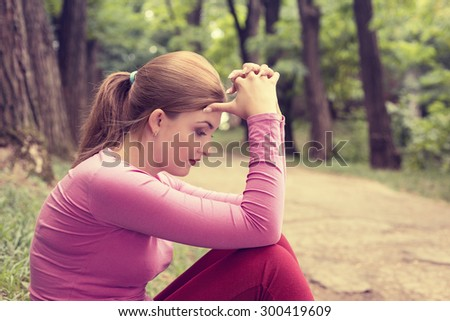 portrait stressed sad young woman sitting outdoors on summer day in park  - stock photo