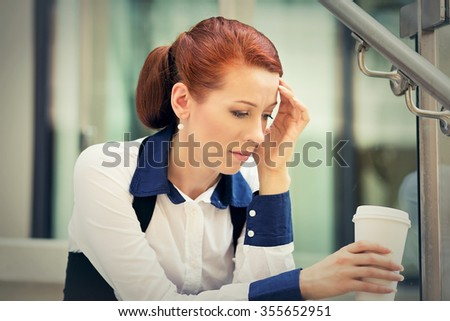 Portrait stressed sad young woman with coffee cup sitting outdoors. City urban life style stress - stock photo
