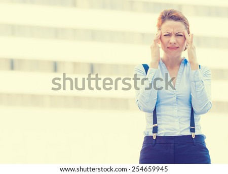 Portrait stressed worried young woman corporate employee having headache migraine  isolated outdoors on corporate office windows building background. Negative human emotions face expression   - stock photo