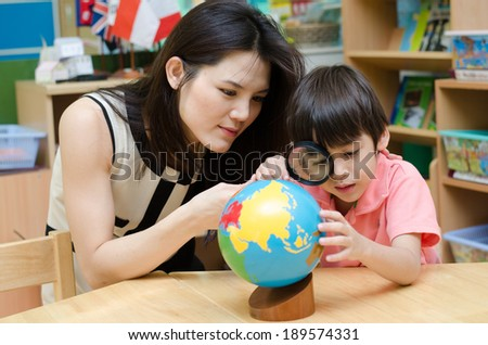 Portrait student looking at globe while listening to teacher with magnifying glass  - stock photo