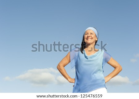 Portrait successful beautiful looking middle aged woman confident, happy and relaxed smiling, enjoying active retirement, isolated with blue sky as background and copy space. - stock photo