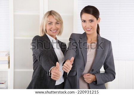 Portrait: Successful business woman team making thumbs up gesture. - stock photo