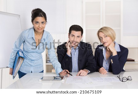 Portrait: successful smiling business team of three people; man and woman in the office wearing commercial blue business outfit.