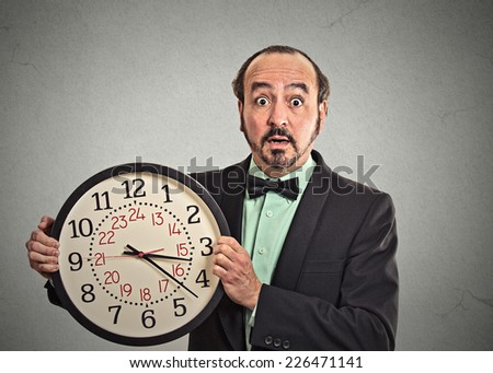 portrait surprised business man in suit holding wall clock isolated grey wall background. Race against time, time goes by, running out of time, no time for work, time running, time is money concept  - stock photo