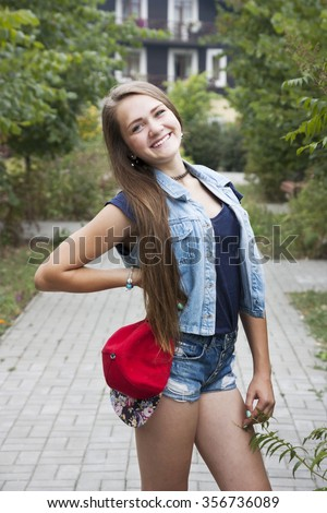 Portrait teen girl in a red cap with beautiful hair