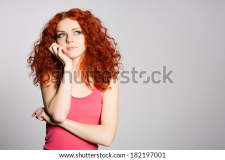 Portrait thinking red haired young woman on a background of gray wall. - stock photo