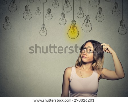 Portrait thinking woman looking up with light idea bulb above head isolated on gray background  - stock photo